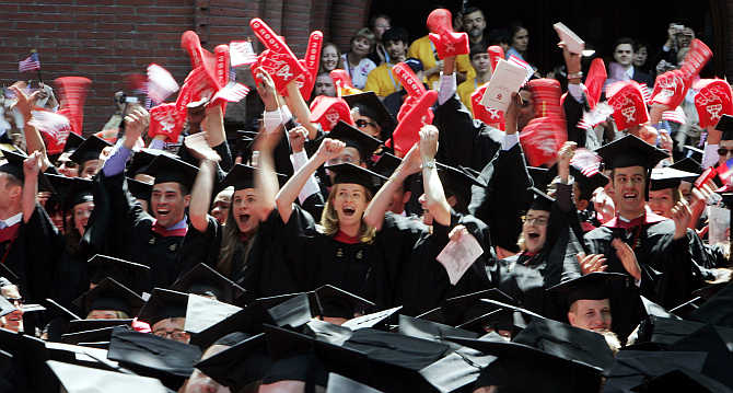 Students from the Harvard Business School cheer as they receive their degrees in Cambridge, Massachusetts.