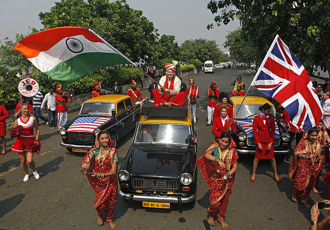 Virgin Group founder Richard Branson waves an Indian national flag while sitting atop a taxi in Mumbai.