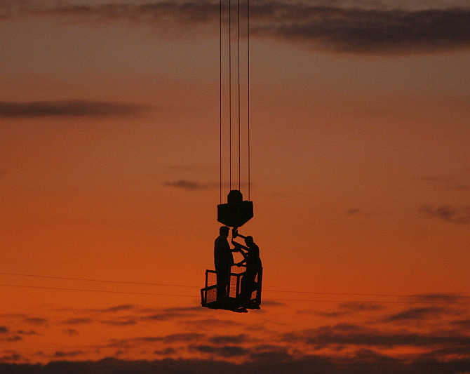 Labourers stand on a winch of a crane at a construction site on the outskirts of New Delhi.