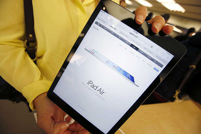 A customer holds iPad Air tablet inside the Apple Store on New York's Fifth Avenue.