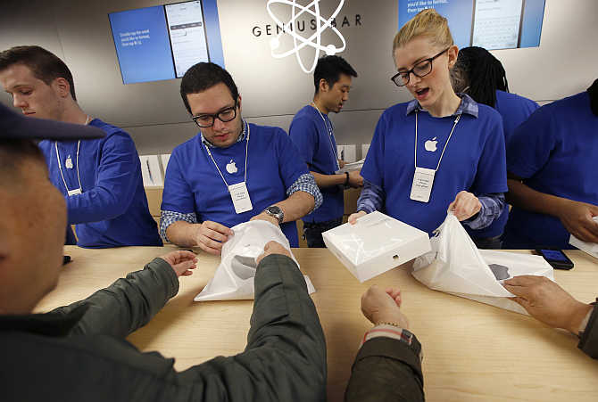 Employees help customers buying iPad Air tablets inside the Apple Store on New York's Fifth Avenue.