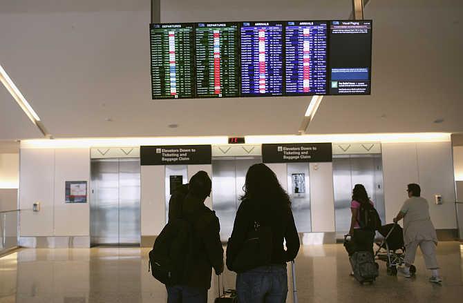 Airline passengers look at a flight status board at San Francisco International Airport in San Francisco, California.