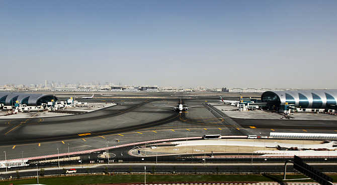 A plane passes in between the Emirates Airlines terminal, left, and a terminal dedicated for A380 aircraft, right, at the concourse in Dubai International Airport.