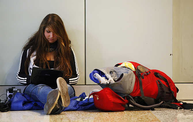 German backpacker Lisa Berkemeyer uses her laptop at the Qantas domestic terminal in Sydney's airport.
