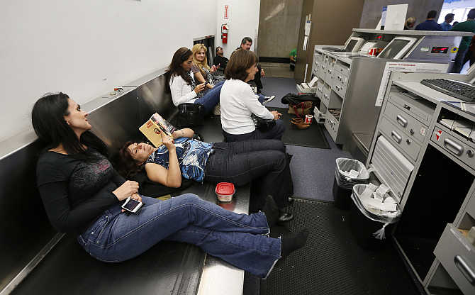 Delayed passengers sit on a baggage conveyer belt at Los Angeles airport in California.