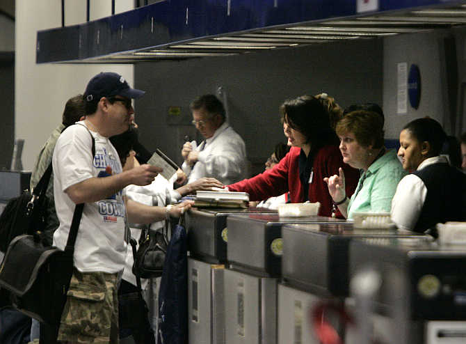 Ticketing agents talk with travellers at Dallas/Fort Worth International Airport in Gapevine, Texas.
