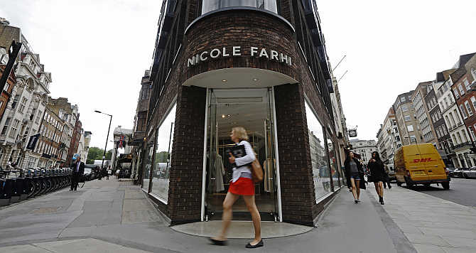 Pedestrians walk past a branch of fashion chain Nicole Farhi in central London.