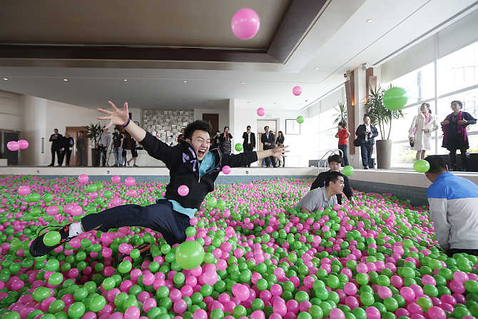A man jumps in a swimming pool filled with pink and green plastic balls during a Guinness World Records attempt of the Largest Ball Pit in Pudong, Shanghai.