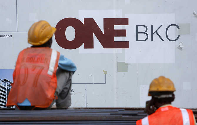 Workers sit in front of an advertising hoarding in the Bandra-Kurla Complex in Mumbai.
