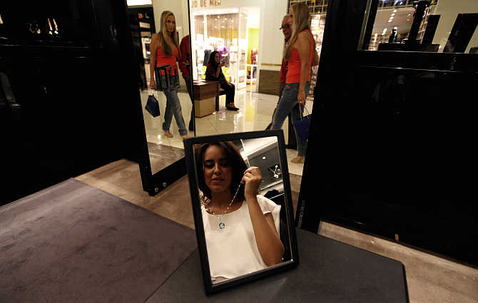 A woman tries on a necklace inside a jewellery store at the Iguatemi mall in Sao Paulo.