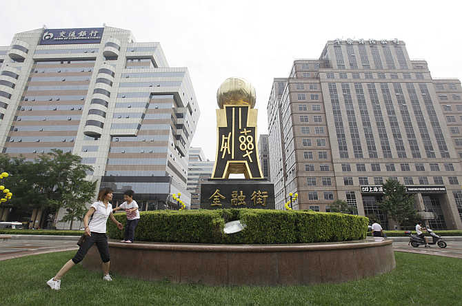 A woman plays with her child next to a statue of ancient Chinese coins at Beijing's Finance Street.