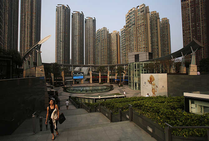 A woman walks up the stairs as luxurious high rise residential buildings are seen at Hong Kong's West Kowloon district.