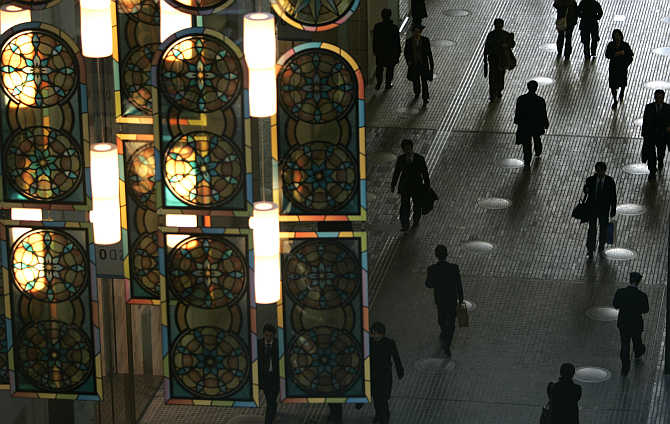 Office workers walk under a decorated illumination in Tokyo's Marunouchi business district.