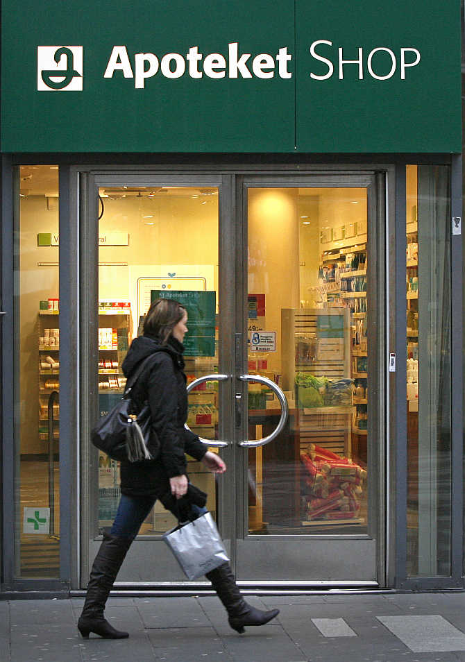 A pedestrian walks past a branch of Sweden's government-owned Apoteket pharmacy chain in downtown Stockholm.