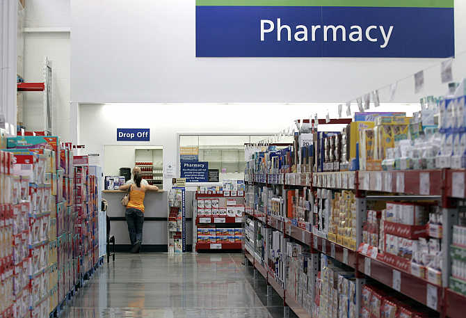 A customer leans against the pharmacy counter at a Sam's Club store in Bentonville, Arkansas.