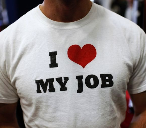 A recruiter for software a company wears a t-shirt as he meets job seekers at a career fair.