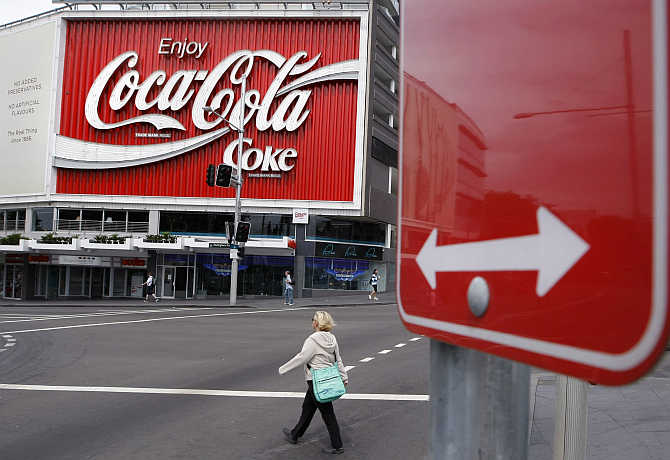 A pedestrian crosses a road in front of an outdoor Coca-Cola advertisement in Sydney.