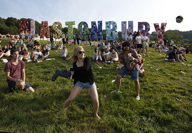 Festival goers play rounders with a wellington boot and a beer can at the Glastonbury music festival at Worthy Farm in Somerset, United Kingdom.