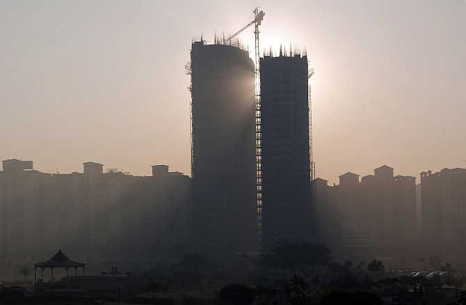 Sun rays beam through two under construction residential buildings in Noida.