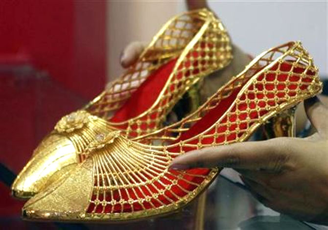 An employee displays a pair of gold footwear at the Gem and Jewellery India International Exhibition in Chennai.