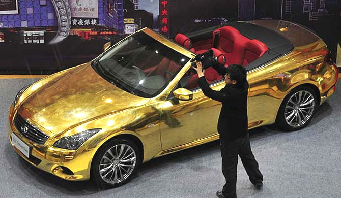 A man photographs a gold-plated Infiniti G37 coupe on show in Nanjing, Jiangsu, China.