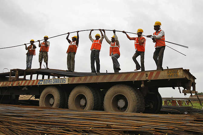 Workers unload iron rods from a truck at a construction site on the outskirts of Ahmedabad.
