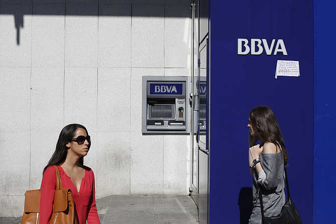 Two women walk past a BBVA bank branch in Madrid, Spain.