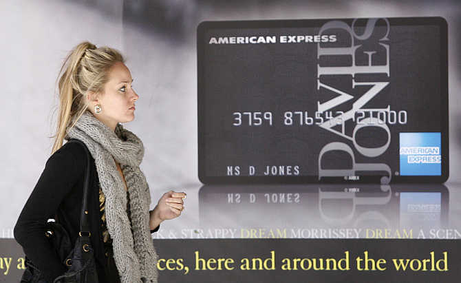 A woman walk past a credit card advertisement in central Sydney.