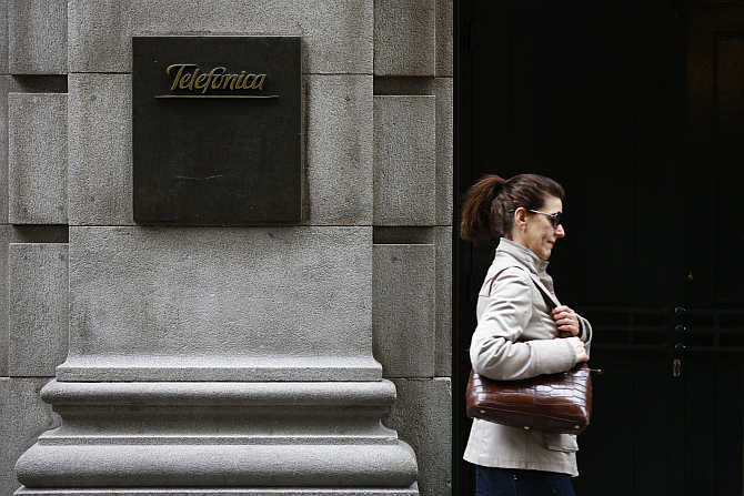 A woman walks past Telefonica's building in central Madrid, Spain.