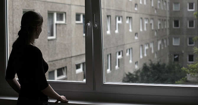 An employee looks out from a window at a hotel in Berlin.