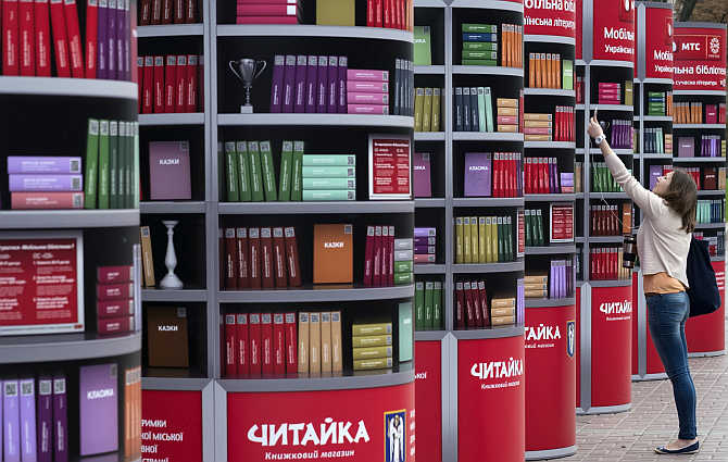 A woman uses her mobile phone to download books in a free mobile library in central Kiev, Ukraine.