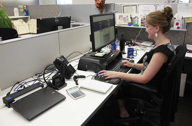 Danelle Hutton works on her laptop computer in her open cubicle at the US National Renewable Energy Laboratory Research Support Facility in Golden, Colorado.
