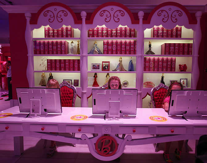 Six-year-old Lara plays with a computer inside a 'Barbie Dreamhouse' of Mattel's Barbie dolls in Berlin, Germany.