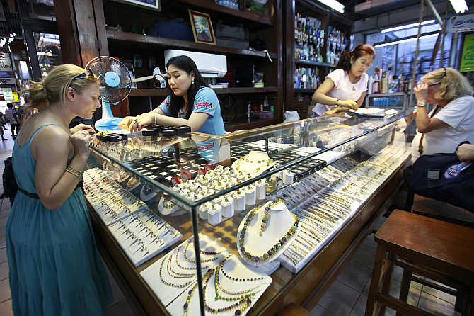 Tourists look at jade and gems in a shop at Aung San market in Yangon, Myanmmar. The Nagarathars moved to Myanmmar in the 19th century.
