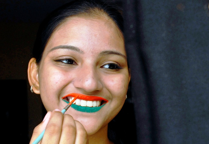 A woman has her lips painted in tri-colours of India's national flag ahead of the Independence