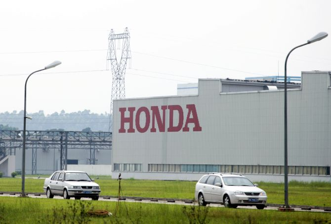 Cars drive past Honda Auto Parts Manufacturing Co. Ltd. plant in Foshan.