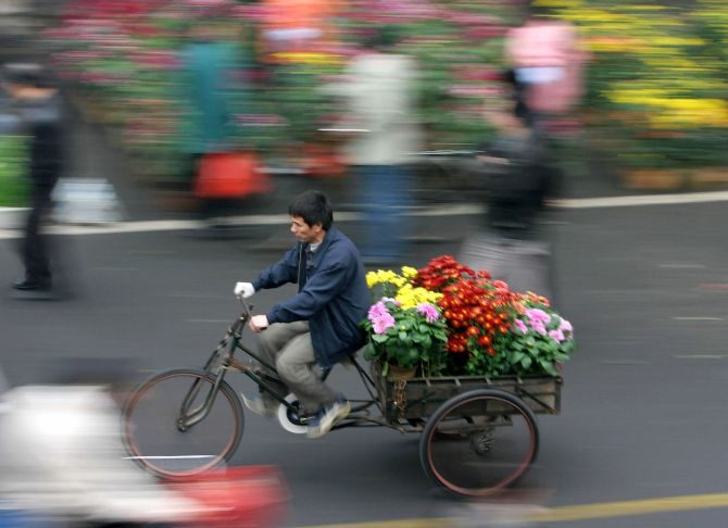 A Chinese man carries flowers in Foshan.