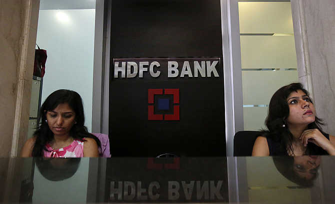 Personal bankers wait for customers at the reception of a HDFC Bank branch in Mumbai.