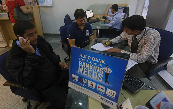 A personal banker speaks to customers inside an HDFC Bank branch in Mumbai.
