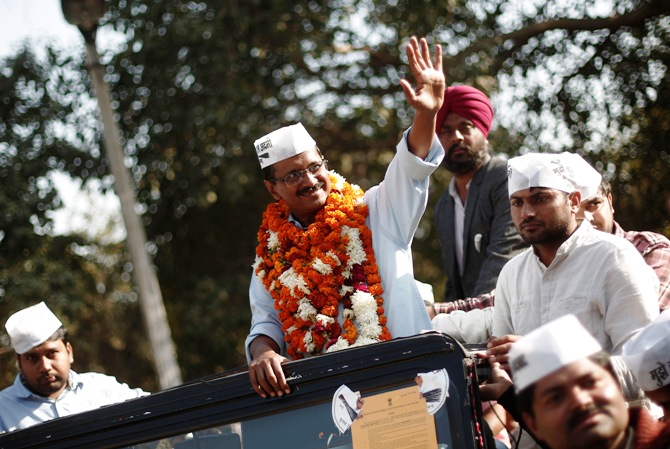 Arvind Kejriwal waves towards his party supporters during a rally.