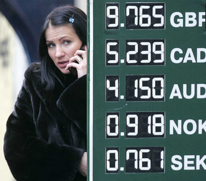 A woman talks on a phone next to a sign displaying currency exchange rates.