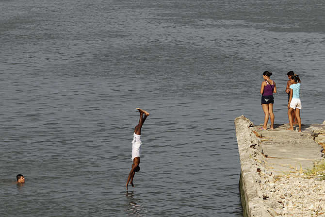 A man dives into the waters of Panama Bay in Panama City, Panama.