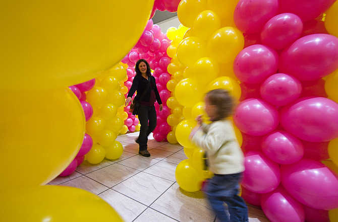 A woman and her child play inside a temporary labyrinth at a shopping mall in Allaman near Lausanne, Switz