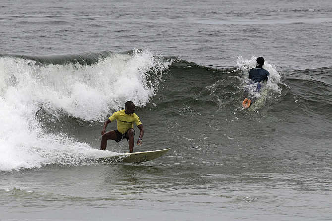 Competitors ride waves at the third annual Surf Liberia Contest at Robertsport in Liberia.