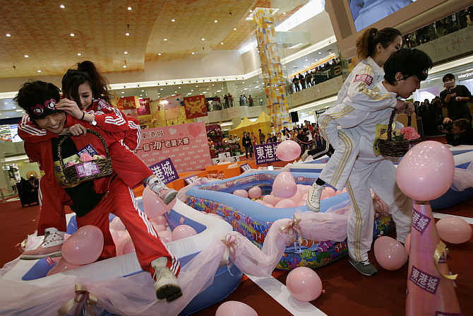 Participants compete in a wife-carrying obstacle race at a shopping mall in Hong Kong.