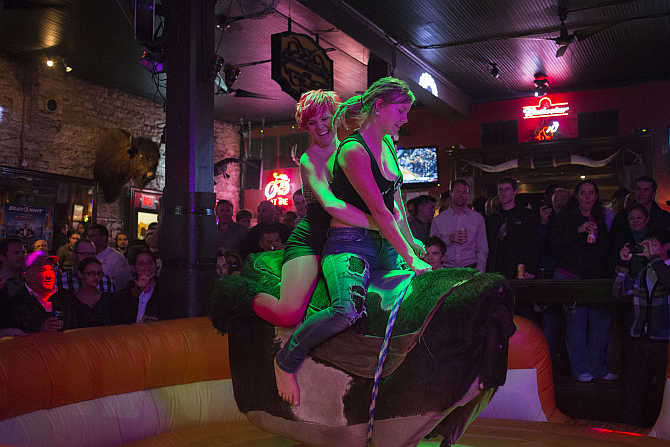 Visitors to a bar ride a mechanical bull on Sixth Street in Austin, Texas, United States.