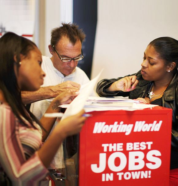 People fill out job application forms at a job fair in Los Angeles, California.