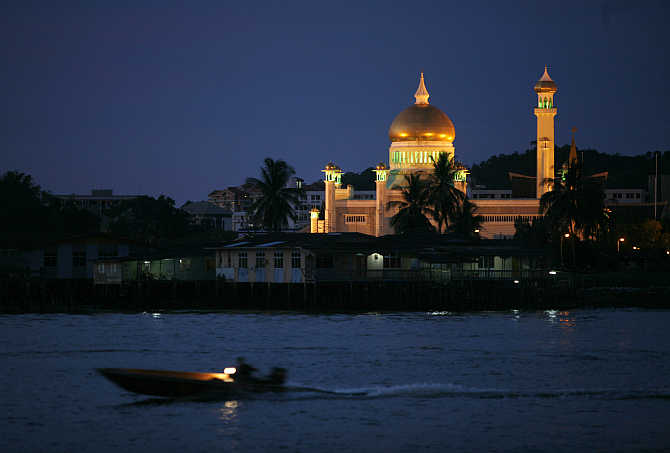 A water taxi passes Brunei's landmark Sultan Omar Ali Saifuddien Mosque in Bandar Seri Begawan, Brunei.