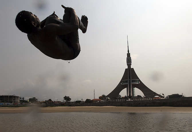A boy plays on the beach in front of the Freedom Tower in Bata, Equatorial Guinea.