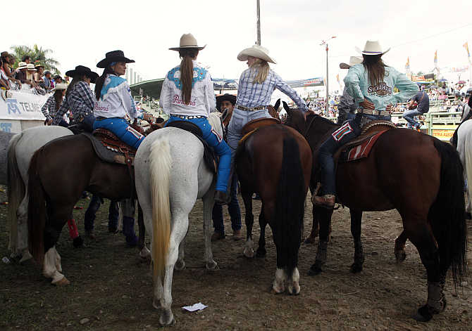 Competitors look on from their horses before competing in the Cowgirl World Championship in Villavicencio, Colombia.